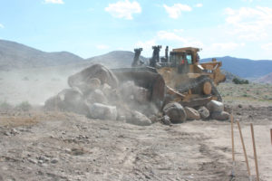 A bulldozer moves boulders as part of the groundbreaking ceremony for the USA Parkway extension project.
