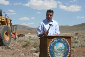 With the future pathway of the road behind him, Gov. Brian Sandoval speaks during the groundbreaking ceremony for the USA Parkway extension project