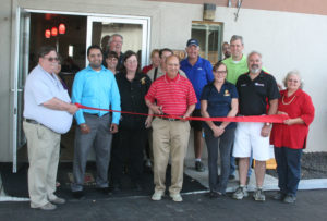 Robert Perea, The Fernley Reporter Super 8 Motel owner Vijan Vohra prepares to cut the ribbon while joined by his son Kartik and several other city business leaders during the Open House for the newly renovated hotel Thursday afternoon,