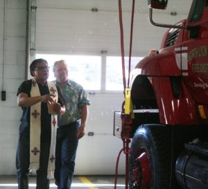 Father Jossph Infante blesses the new fire engine with holy water,
