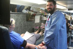 Phlebotomist Ben Valentine talks with blood donor Jessie Wagner .